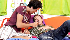 Pretty young and very handsome gay boys are kissing in the bed