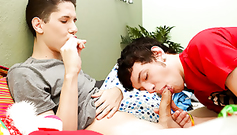 A gay boy is sucking candy while his boyfriend is sucking his dick