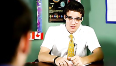 Sexy young gay is sitting on the desk and enjoying blowjob